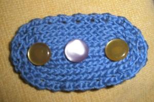 Απλή καρφίτσα πλεγμένη με βελονάκι πάνω σε παραμάνα με τρία κουμπάκια για στόλισμα